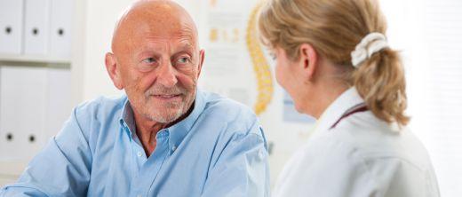 Älterer Mann sitzt beim Arzt